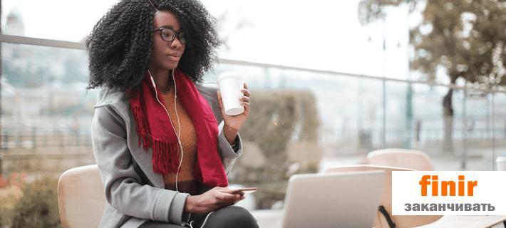 Девушка пьёт кофе перед ноутбуком