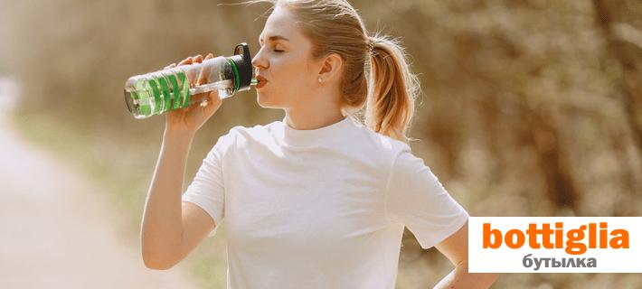 Девушка пьёт воду с бутылки