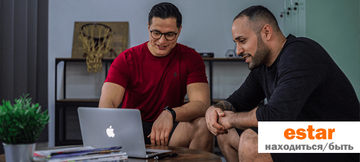 Двое мужчин сидит перед ноутбуком
