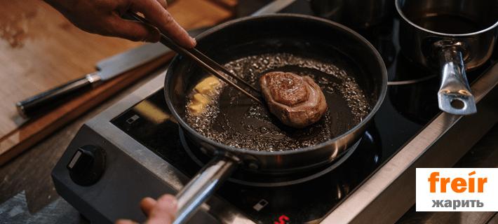 Мужчина жарит мясо на сковородке