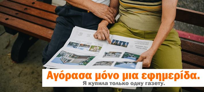 Пенсионеры читают газету на лавочке