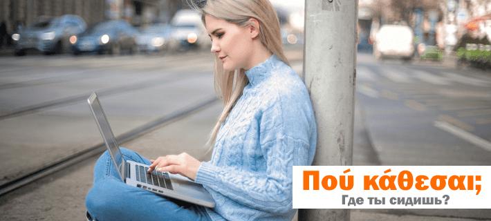 Девушка сидит на асфальте с ноутбуком